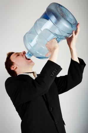 Man drinking water from huge water bottle